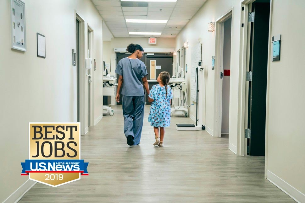 Nurse and child in hospital corridor